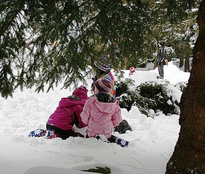 Kinder sitzen unter einem Baum im Schnee